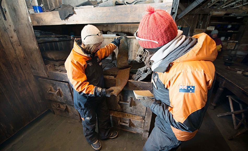 Restauratorin Nicola Dunn und Projekt Manager Lizzie Meek notieren die Position von Objekten, in diesem Fall ein Paar Stulpen, in Scott, Hütte bei Cape Evans. Foto: Alasdair Turner