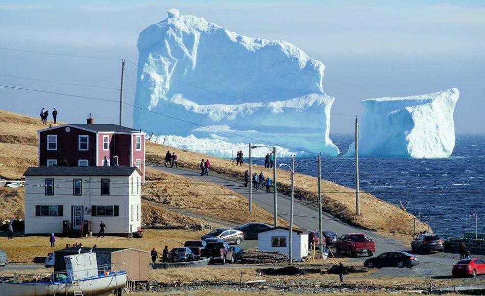 Die Kleinstadt Ferryland ist zu einem Touristenmagnet geworden aufgrund der Eisberge vor der neufundländischen Küste. Diese überragen die Häuser bei weitem. Bild: Reuters