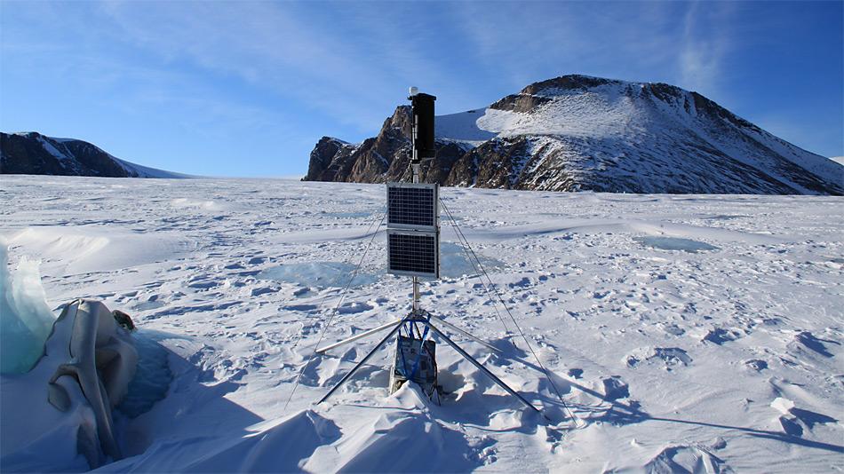 Passive Seismik/ GPS Station am A.P. Olsen Ice Cap. Zu sehen sind (von oben beginnend) GPS Antenne, Windrad, Solar Panels und die Alukiste, in der sich Messgeräte befinden. Foto: ZAMG/Daniel Binder