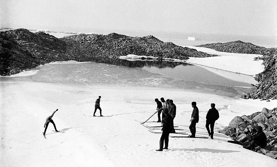 Australische Skifahrer auf dem antarktischen Kontinent. Landeinwärts südöstlich der Basisstation bei Cape Denison. Im Hintergrund ein während des antarktischen Sommers aufgetauter Gletschersee (Xavier Mertz, wahrscheinlich Mitte Februar 1912; Continental Size; Mitchell Library, State Library of New South Wales).